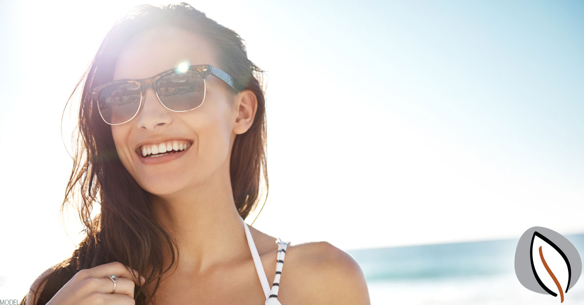 Woman smiling wearing sunglasses.